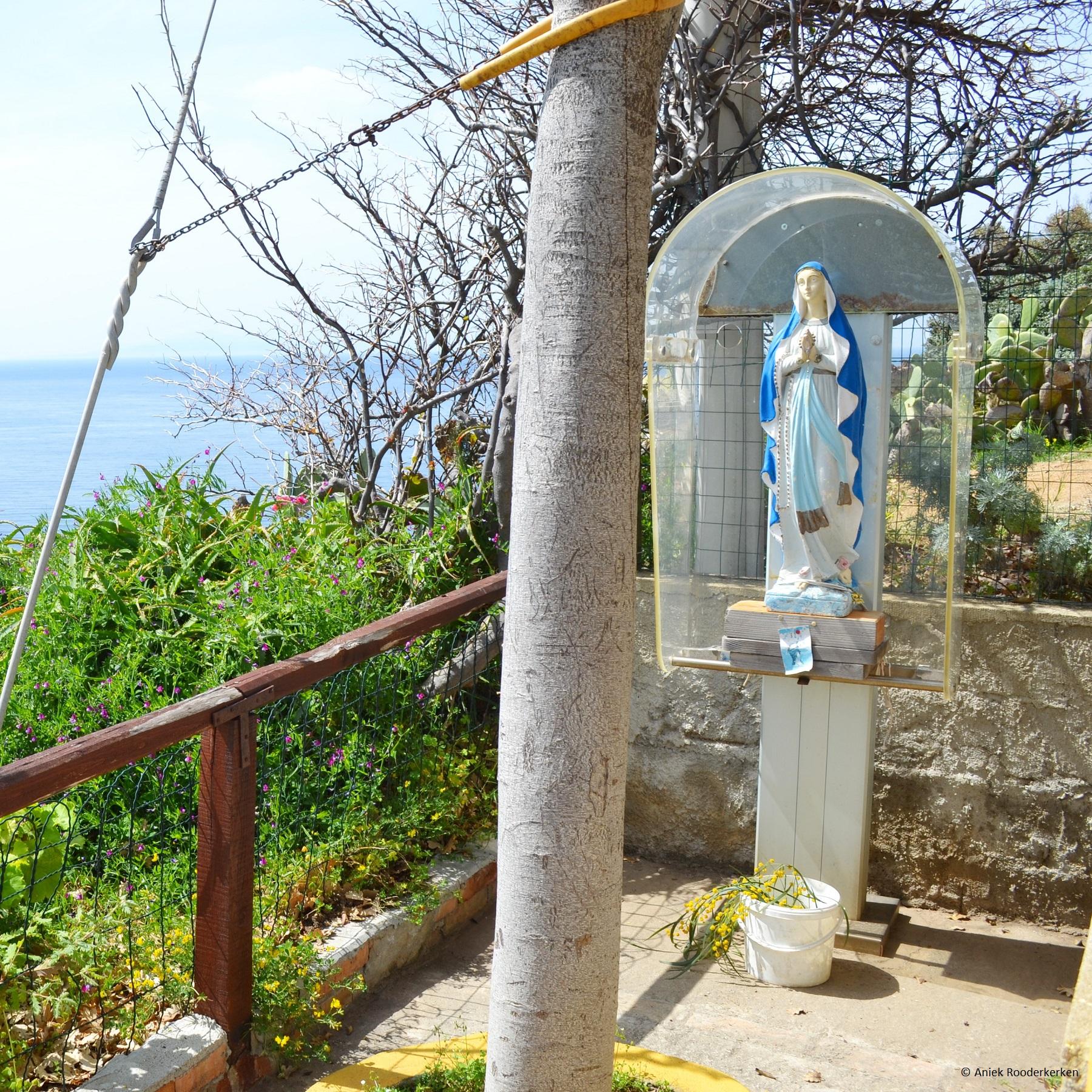 De oude telefooncel, die nu beschutting biedt aan een Mariabeeld