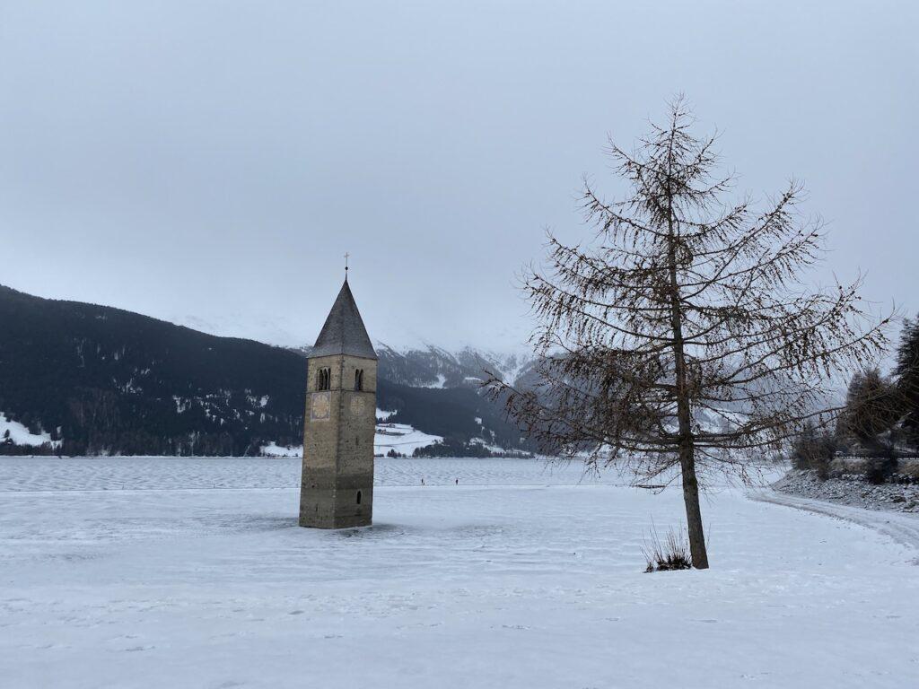 Het kerkje in het Reschenmeer in de winter