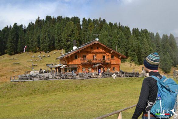 Wandelaar voor een berghut in Zuid-Tirol